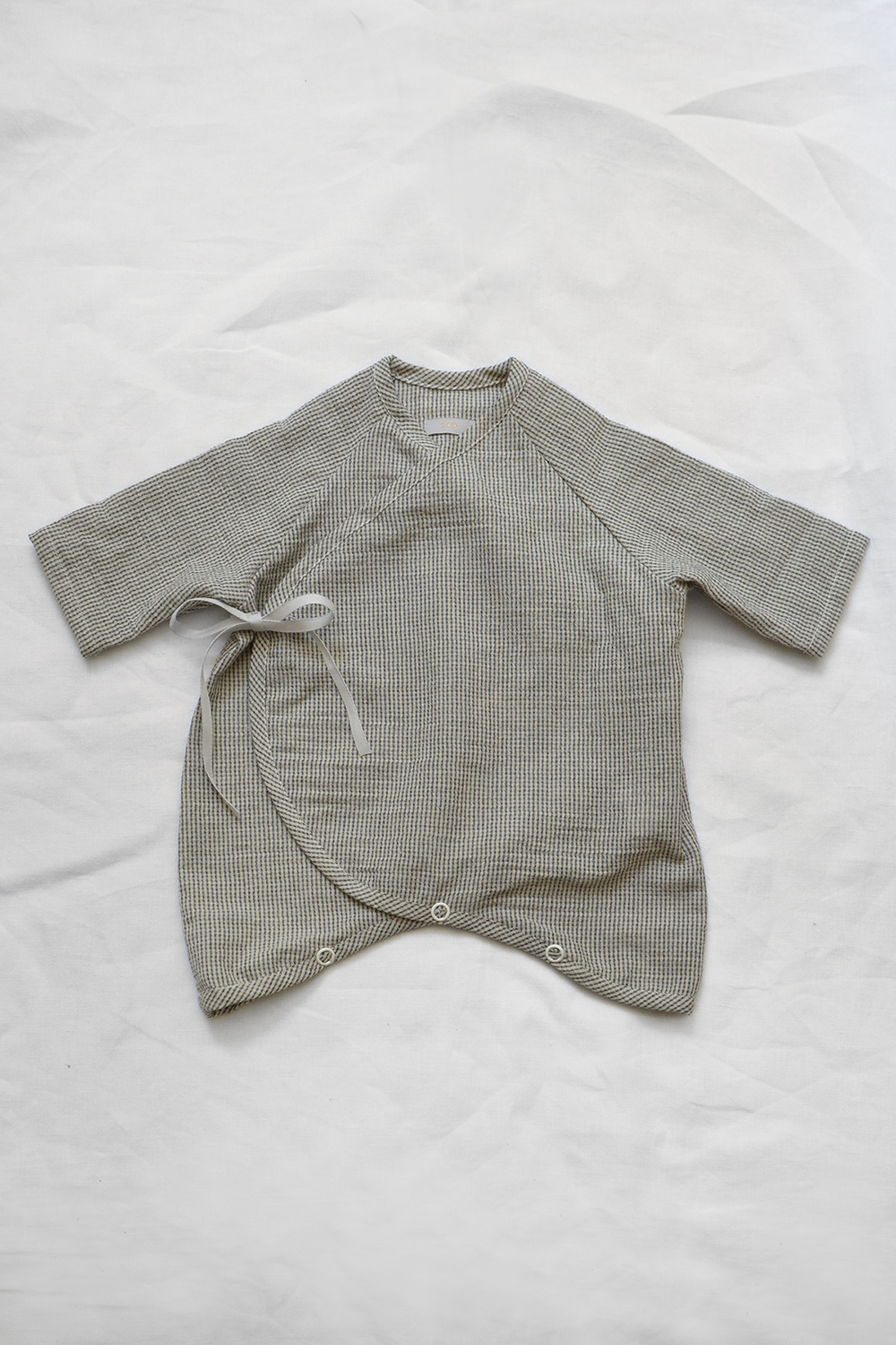 """Light weight and highly breathable baby kimono onesie """"Penn"""" in charcoal check laid flat on a white background. A GOTS certified baby clothes by Makie."""
