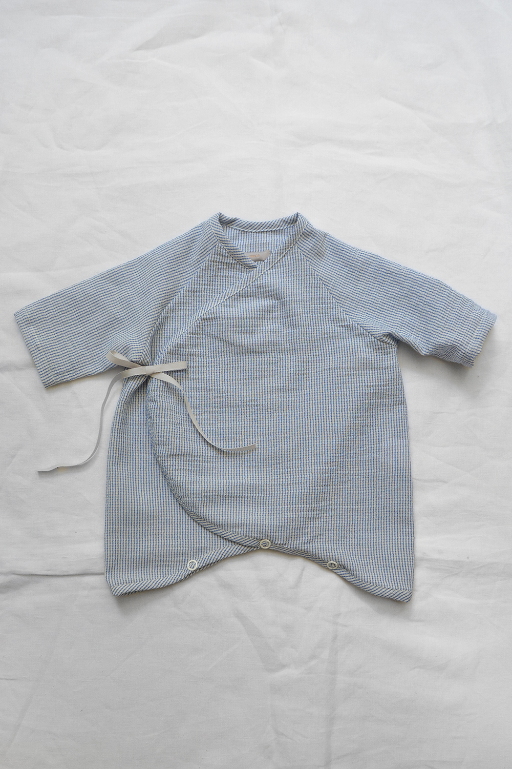 """Light weight and highly breathable baby kimono onesie """"Penn"""" in blue check laid flat on a white background. A GOTS certified baby clothes by Makie."""